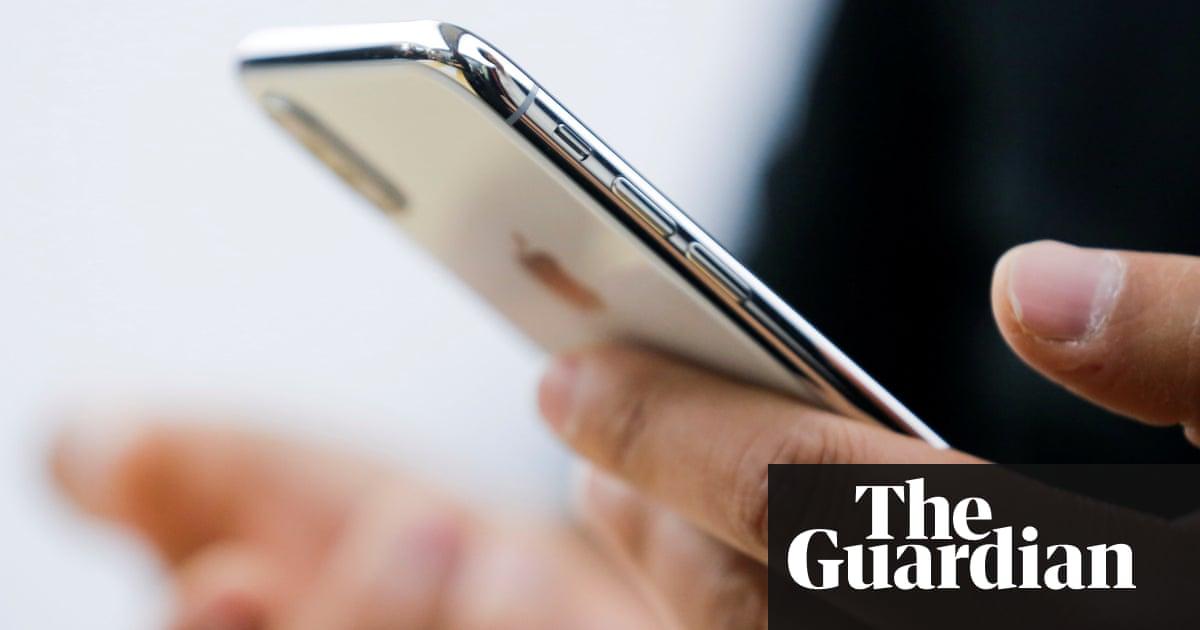 Mano sosteniendo un iPhone XS con el logotipo de The Guardian