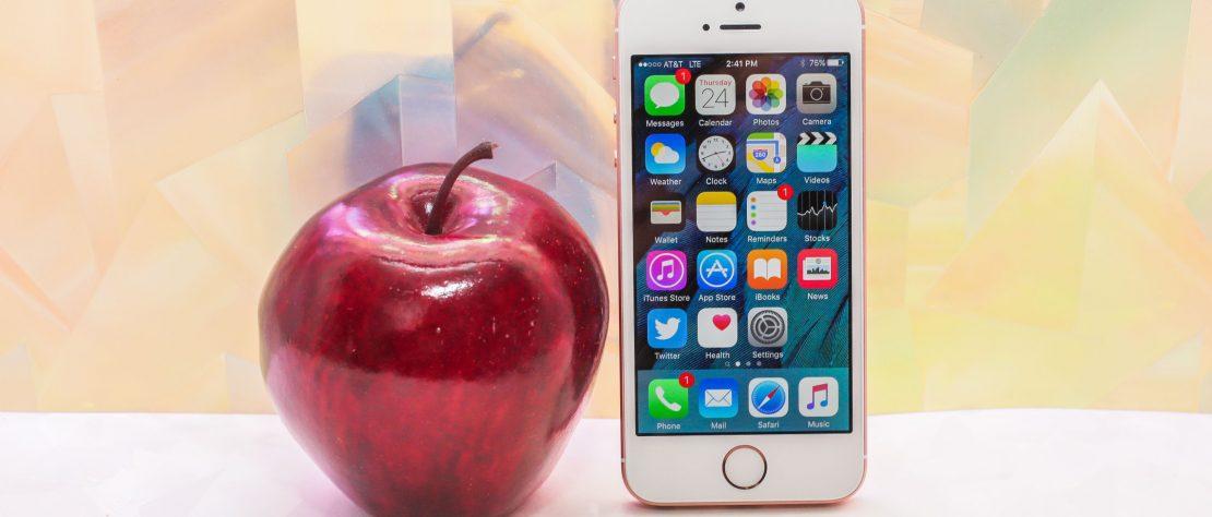 Una manzana roja a un lado del iPhone SE