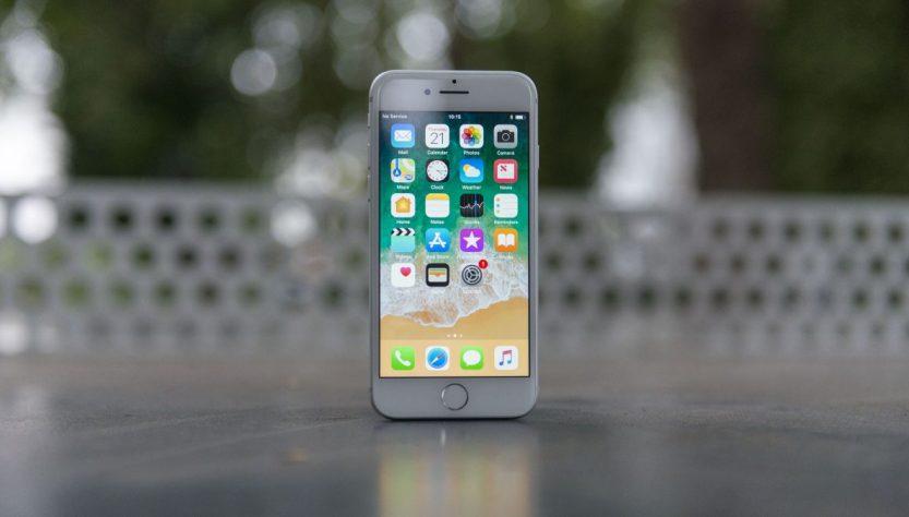iPhone 8 blanco colocado en una mesa, el celular se encuentra encendido