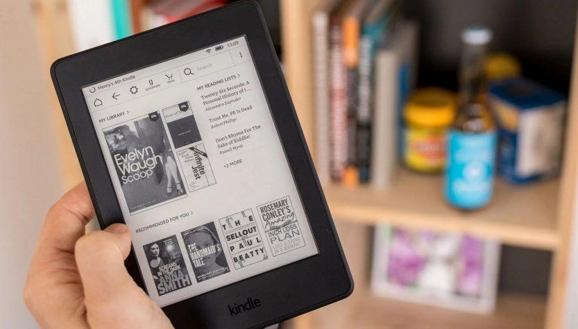 Kindle de Amazon en la mano de una mujer con revistas abiertas para la lectura